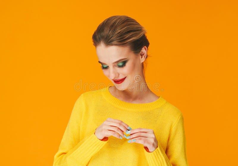 Rote Lippen der bunten Make-upfrau in der gelben Kleidung auf Farbglücklichem Sommer-Modehintergrund manikürten Nägel stockbild