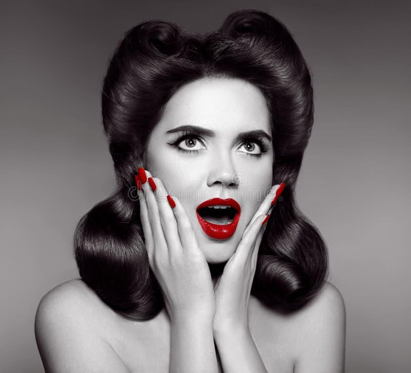Rote Lippen und manikürte Nägel Überraschter Stift herauf Mädchen hält Backen stockfoto