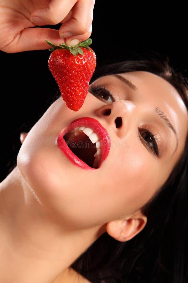 Rote Lippenjunge Frau, die frische Erdbeerefrucht isst lizenzfreies stockbild