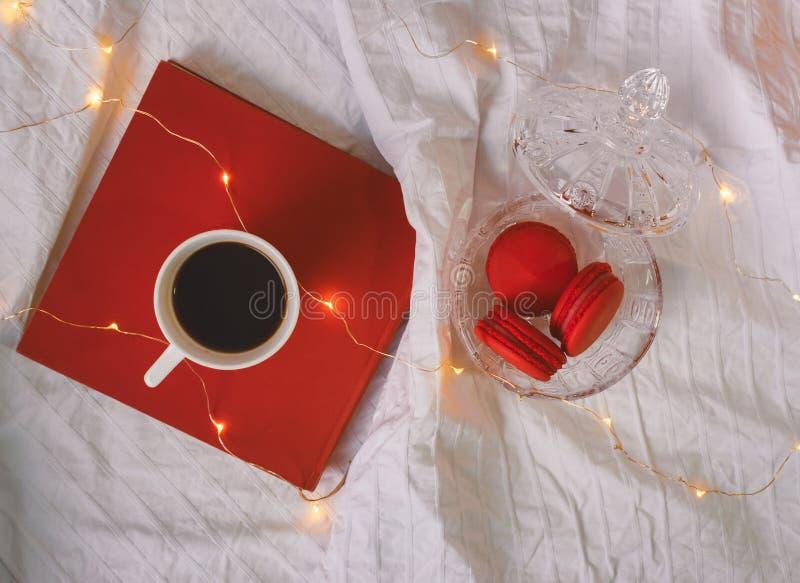 Rote macarons in der Kristallschüssel, im Buch und in einem Kaffee stockfotografie