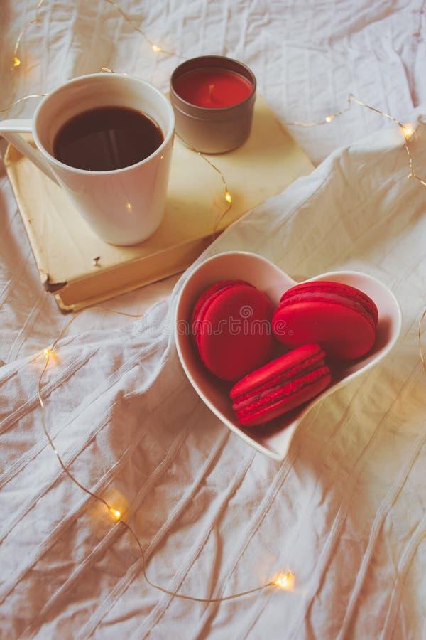 Rote macarons in einem Herzen formten Schüssel, Buch, Kerze und einen Kaffee stockfoto