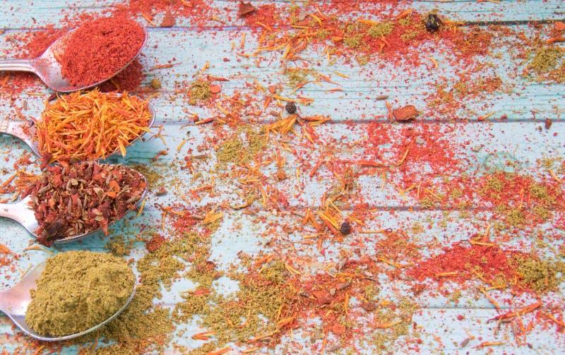 Rote, Mehrfarben-, orange und grüne Gewürze auf dem blauen hölzernen Hintergrund lizenzfreie stockfotografie