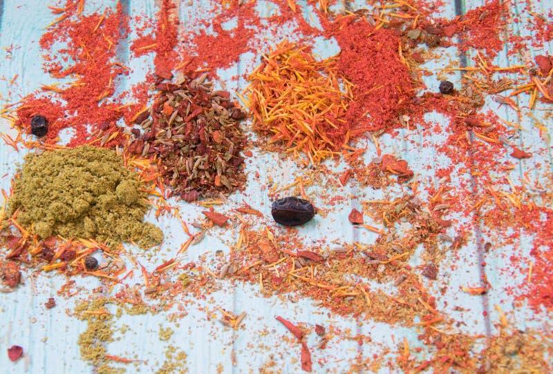 Rote, Mehrfarben-, orange und grüne Gewürze auf dem blauen hölzernen Hintergrund lizenzfreies stockfoto