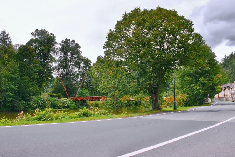 Rote Metallbrücke über Ohre-Fluss und großer grüner Baum in Kyselka-Dorf mit Asphaltstraße 222 auf Vordergrund am Beginn des tsch stockfotos