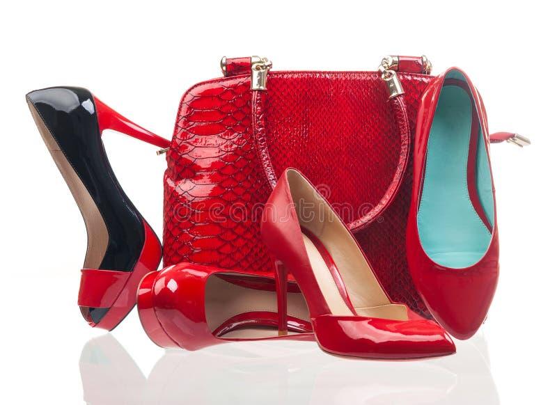 Rote Modefrauenschuhe und -handtasche über Weiß lizenzfreie stockfotos