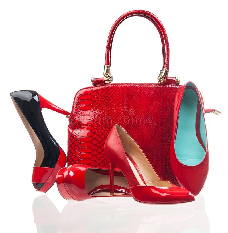 Rote Modefrauenschuhe und -handtasche auf Weiß stockfotografie