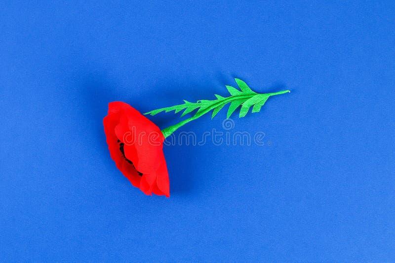 Rote Mohnblume Anzac Day, Erinnerung Diy-Papiers, erinnern sich, Volkstrauertagkrepppapier auf blauem Hintergrund stockbild