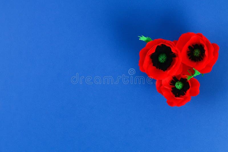 Rote Mohnblume Anzac Day, Erinnerung Diy-Papiers, erinnern sich, Volkstrauertagkrepppapier auf blauem Hintergrund lizenzfreie stockfotos