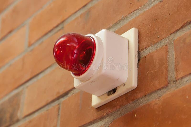 Rote Notbeleuchtung auf einer Backsteinmauer lizenzfreies stockbild