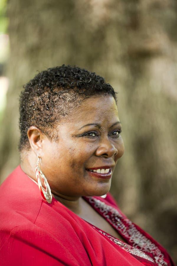 Rote Oberseite des von mittlerem Alter Portraits der schwarzen Frau im Freien stockfoto