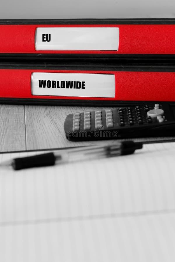 Rote Ordner mit EU und auf den Aufkleber auf einem Schreibtisch weltweit geschrieben stockbilder
