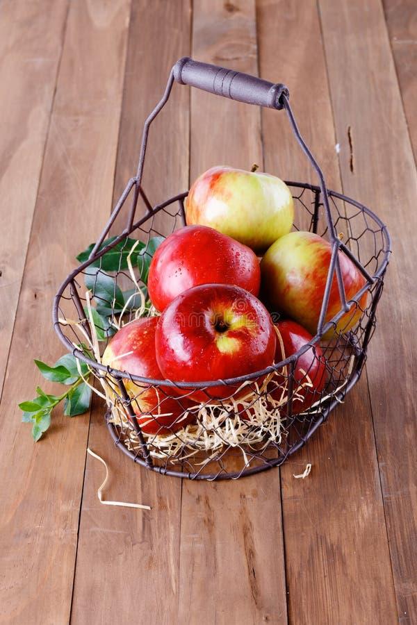 Rote organische Äpfel in einem Metallkorb auf hölzernem Hintergrund stockfotografie