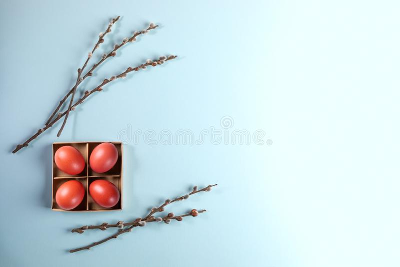 Rote Ostereier in der Pappschachtel mit Weidenniederlassungen auf hellblauem Hintergrund stockbild