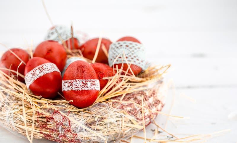 Rote Ostereier in einem Nest des Heus lizenzfreie stockfotos