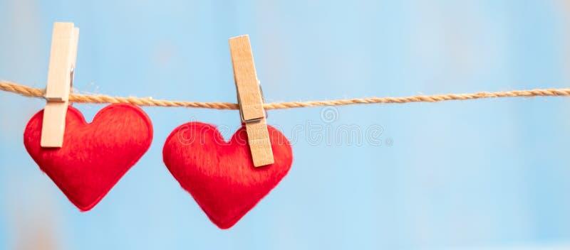 Rote Paarherz-Formdekoration, die an der Linie mit Kopienraum für Text auf blauem hölzernem Hintergrund hängt Liebe, Hochzeit, ro lizenzfreie stockfotos