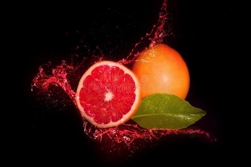 Rote Pampelmuse innerhalb Juice Splashs lizenzfreie stockfotografie