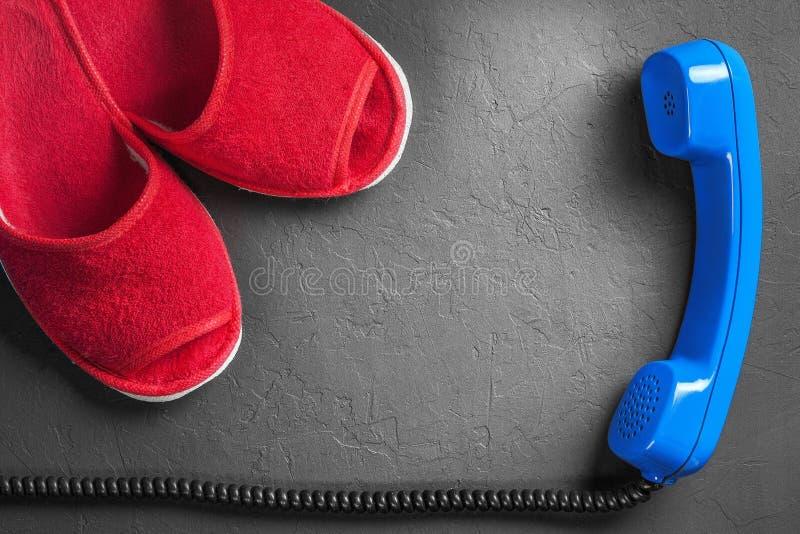 Rote Pantoffel mit Hörer auf Boden lizenzfreies stockfoto