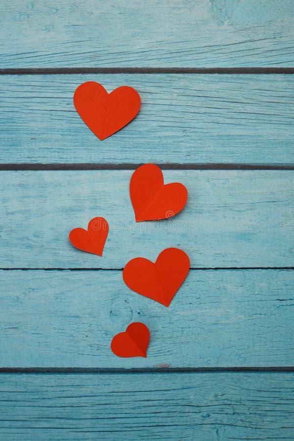 Rote Papierherzen auf einem blauen hölzernen Hintergrund lizenzfreies stockfoto