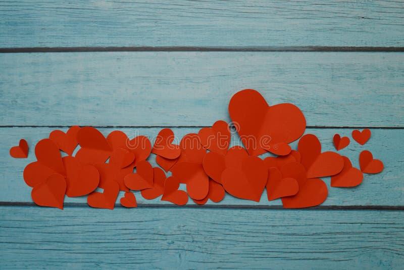 Rote Papierherzen auf einem blauen hölzernen Hintergrund lizenzfreie stockbilder