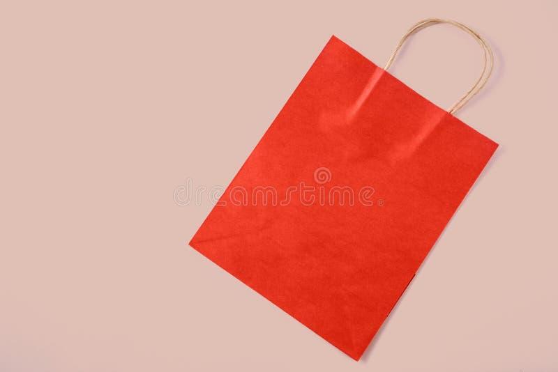 Rote Papiertüte auf beige Hintergrund Beschneidungspfad eingeschlossen stockfotografie