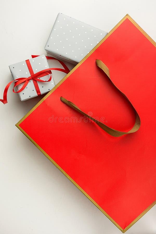 Rote Papiertüte eingewickelter Kästen gekräuselter Band-Bogen Weißer Hintergrundkopienraum Verkaufsrabatt stockfoto