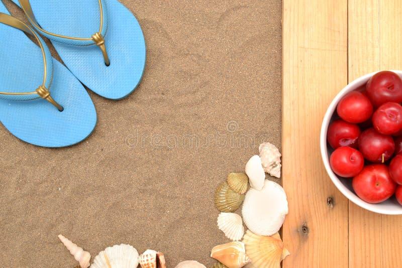 Rote Pflaumen und Oberteile auf Sand lizenzfreie stockbilder