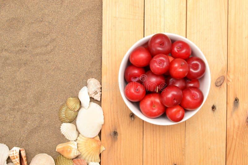 Rote Pflaumen und Oberteile auf Sand lizenzfreies stockfoto