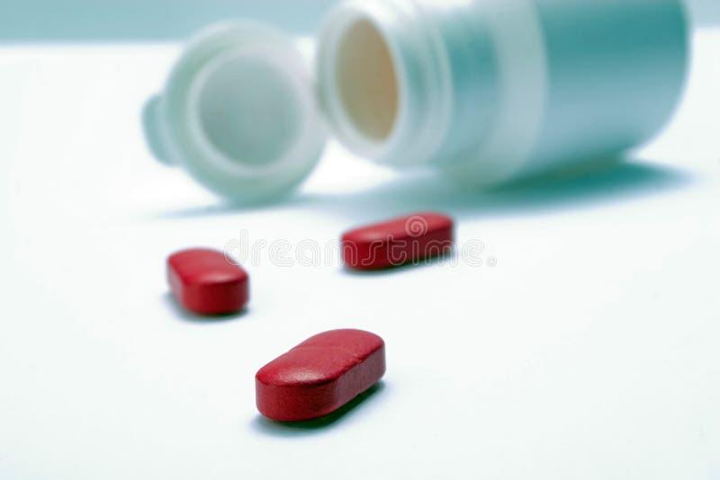 Rote Pillen und eine Flasche stockbild