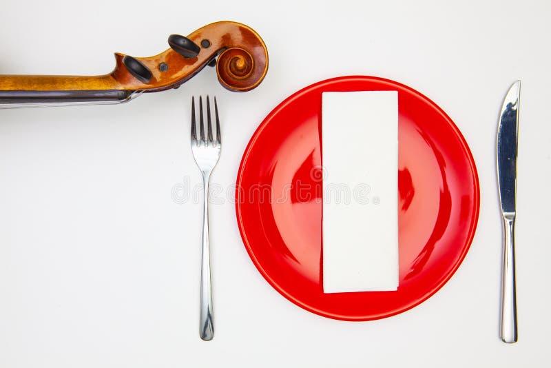 Rote Platte und alte Violine auf dem weißen Holztisch stockfotografie