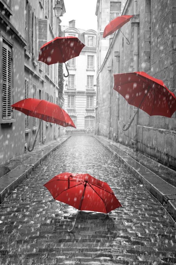 Rote Regenschirme, die auf die Straße fliegen Haus gebildet vom Geld im schwarzen Hintergrund lizenzfreie abbildung