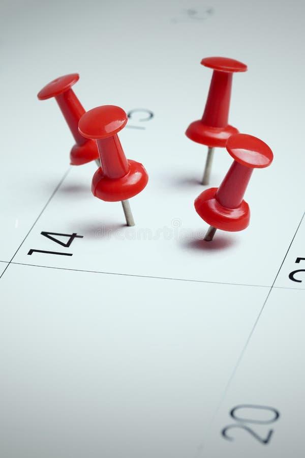 Rote Reißzwecke auf Kalender lizenzfreie stockfotografie