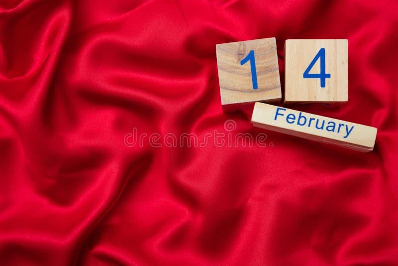 Rote Rose Draufsicht von hölzernen Würfeln des Kalenders mit am 14. Februar Text auf rotem Seidenhintergrund lizenzfreie stockfotografie