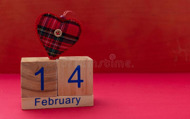 Rote Rose 14. Februar und ein rotes Gewebeherz auf rotem Hintergrund lizenzfreies stockfoto