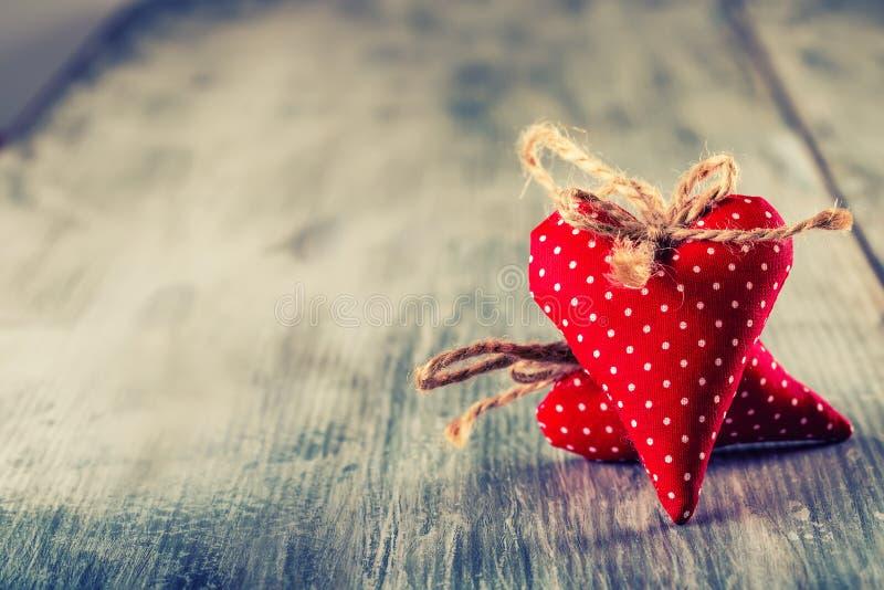 Rote Rose Handgemachte Herzen des roten Stoffes auf hölzernem Hintergrund lizenzfreie stockfotos
