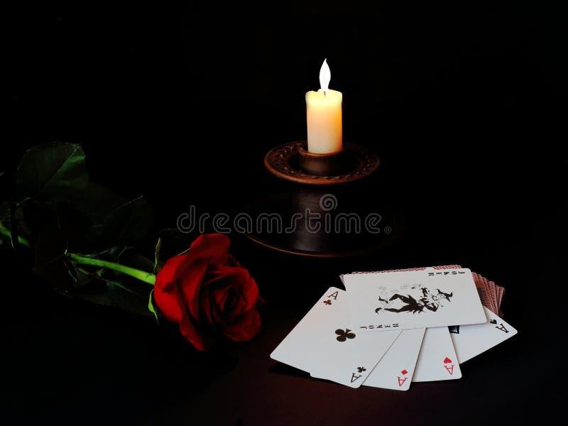 Rote Rose, keramischer Kerzenständer mit brennenden Paraffinkerzen und ein Kartenstapel auf einem schwarzen Hintergrund Symbolisc lizenzfreie stockfotos