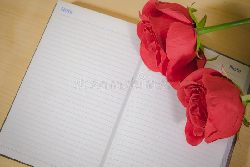 Rote Rose am Notizbuch lizenzfreie stockbilder