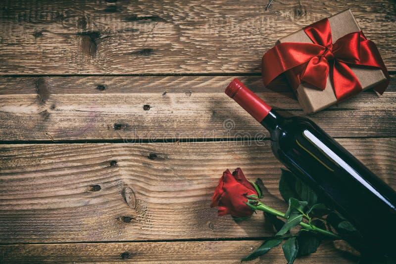 Rote Rose Rotweinflasche, Rosafarben und ein Geschenk auf hölzernem Hintergrund stockfotografie