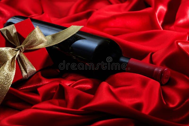 Rote Rose Rotweinflasche und ein Geschenk auf rotem Satin lizenzfreies stockbild
