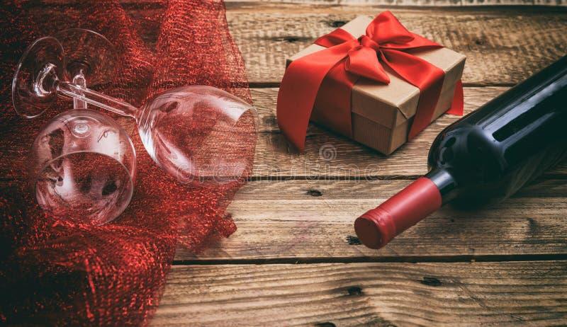 Rote Rose Rotweinflasche und -gläser auf hölzernem Hintergrund stockfotografie