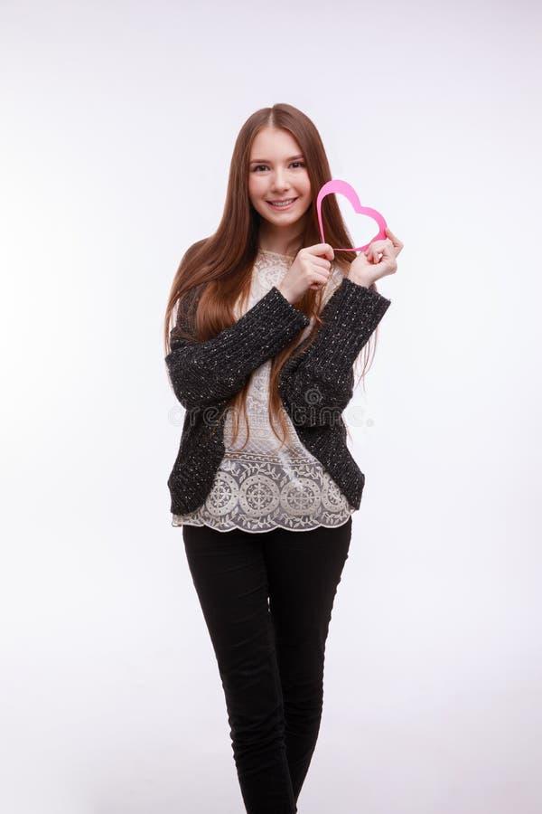 Rote Rose Schließen Sie herauf Ansicht eines glücklichen jungen Mädchens mit rosa Herzen lizenzfreie stockfotos