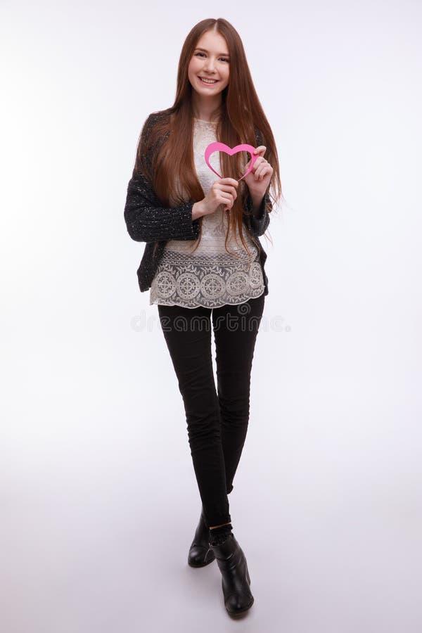 Rote Rose Schließen Sie herauf Ansicht eines glücklichen jungen Mädchens mit rosa Herzen stockbild