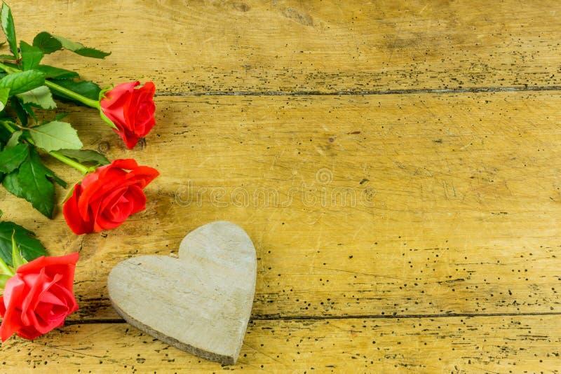 Rote Rosen auf einem alten Brett mit einem Herzen stockfoto