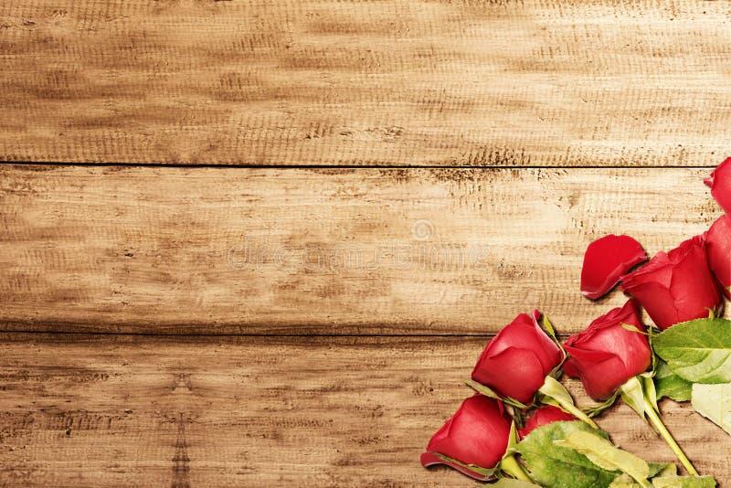 Rote Rosen auf einem Holztisch lizenzfreies stockfoto