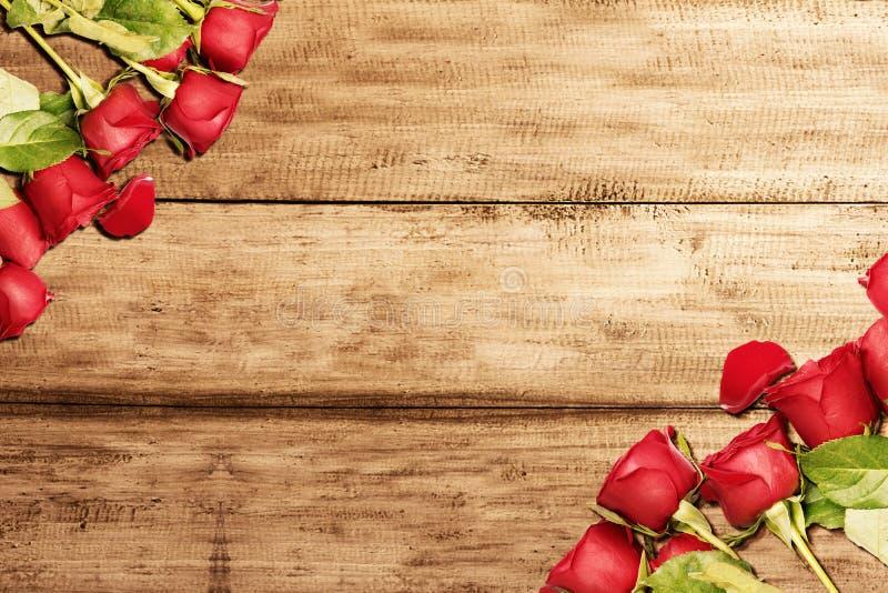 Rote Rosen auf einem Holztisch stockfotos