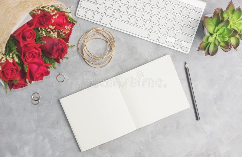 Rote Rosen auf grauer Tabelle mit weißer Tastatur, offenem Notizbuch und boho Schmuck Künstlerarbeitsplatz, Bürokonzept stockbilder