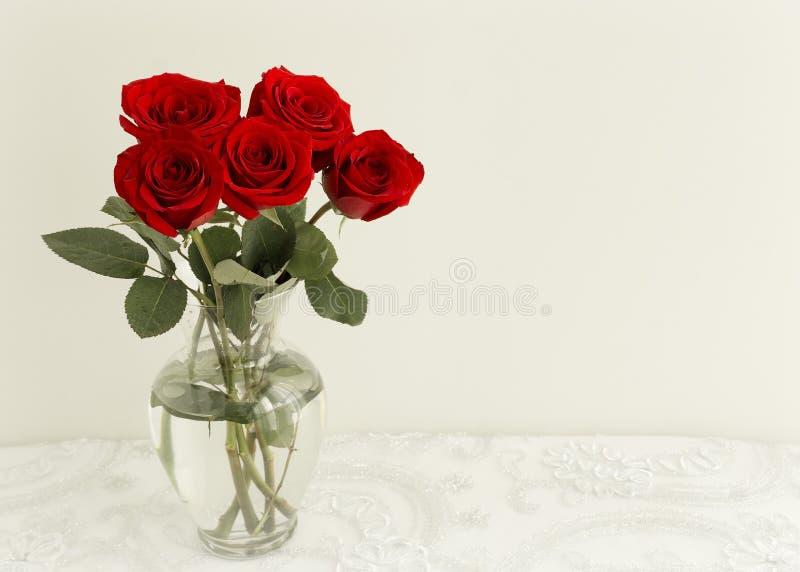 5 rote Rosen im Vase lizenzfreie stockfotos