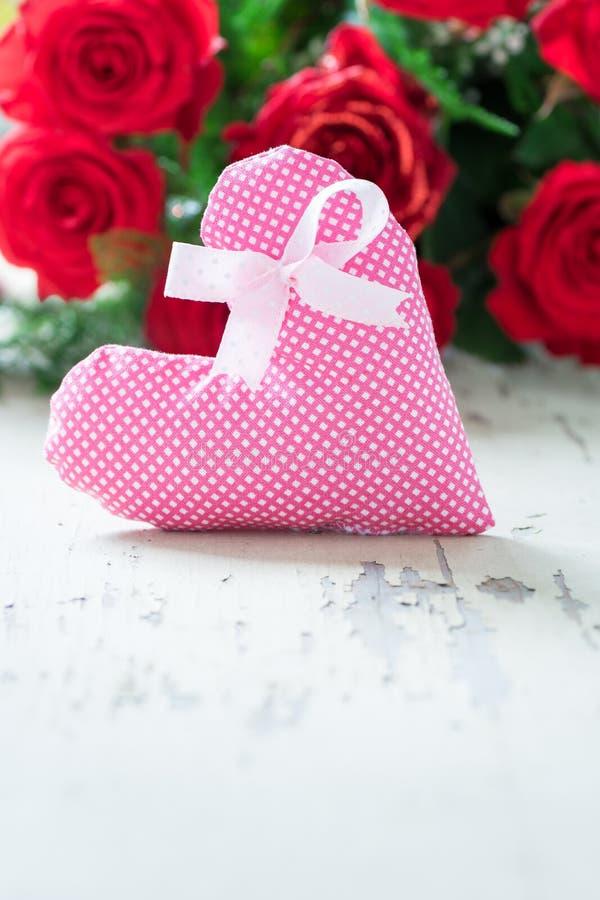 Rote Rosen mit Gewebeherzen - Copyspace stockfotografie