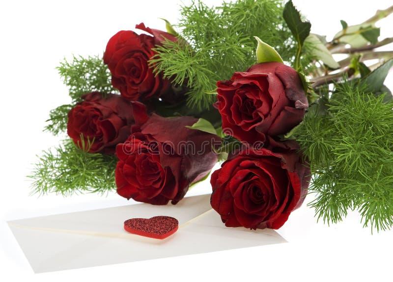Rote Rosen mit Liebesbrief stockfotos