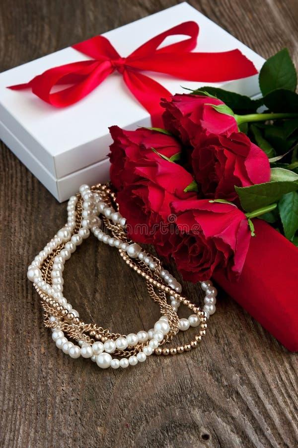 Rote Rosen und Geschenkbox auf hölzernem Hintergrund lizenzfreie stockbilder
