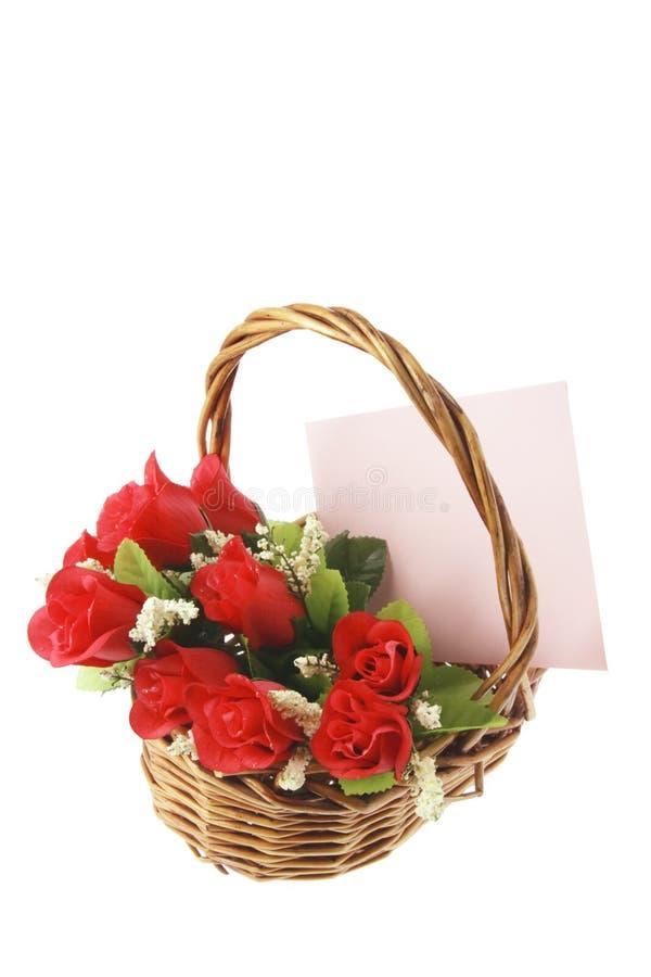 Rote Rosen und Gruß-Karte im Korb stockfoto
